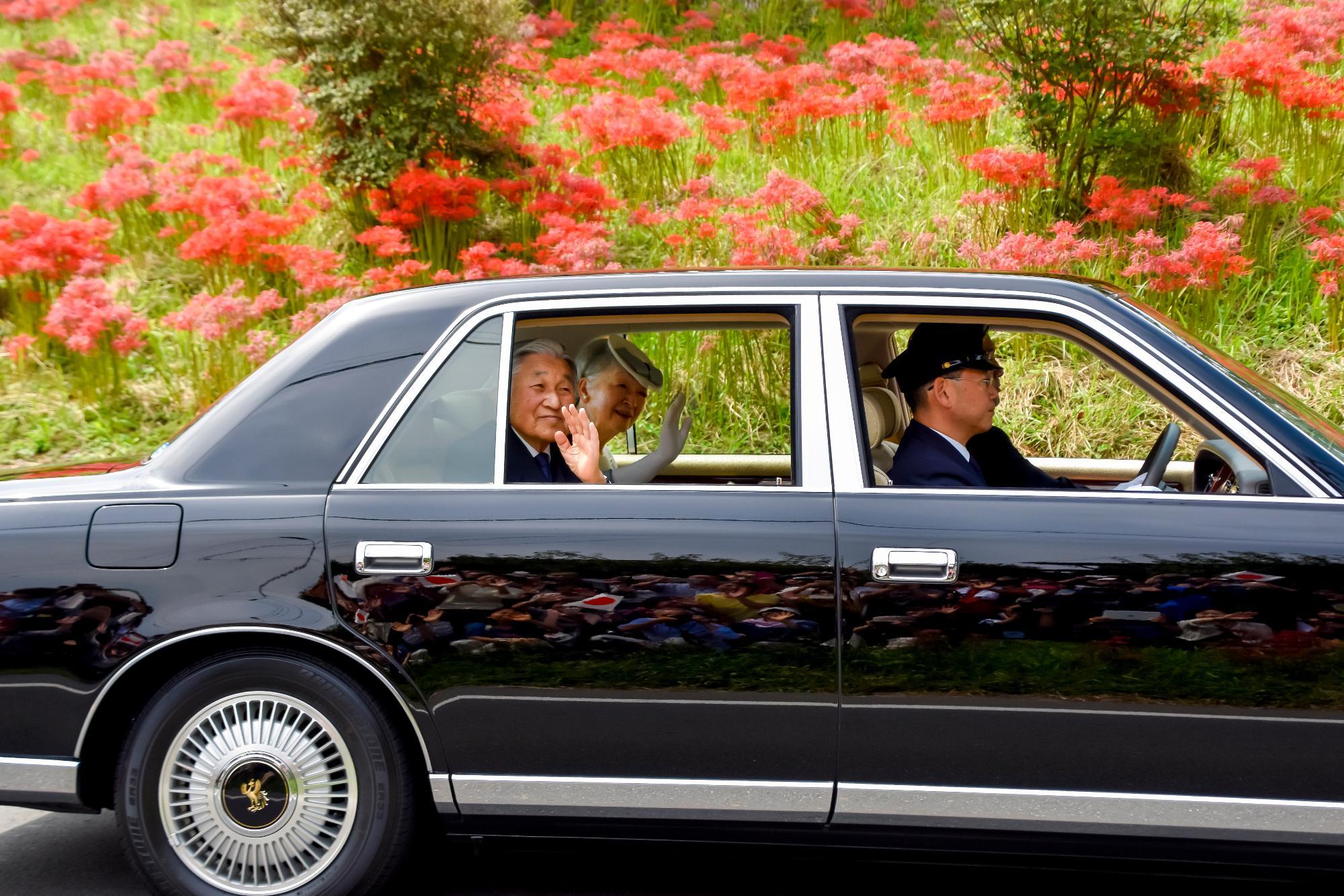 Sus Majestades quienes se ondea la mano a a las personas de la orilla del camino