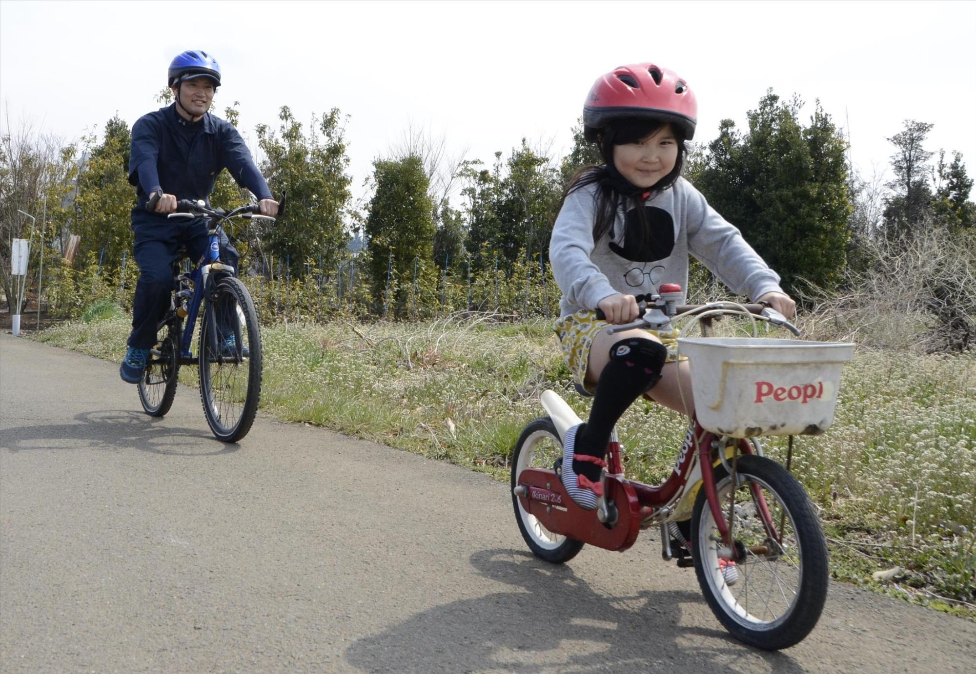 Fotografía de padre y niño que se pusieron un casco y monta una bicicleta